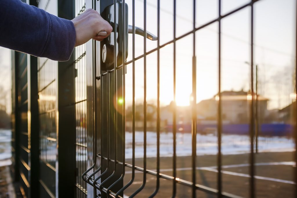 Person Closing a Security Gate