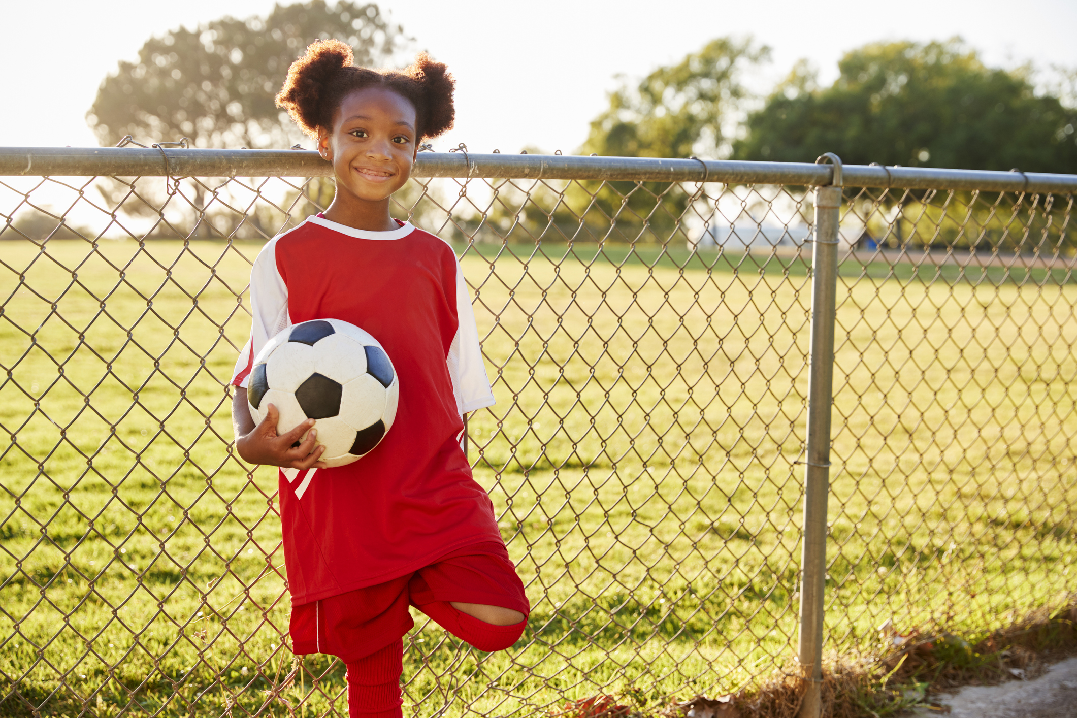Girl holding soccer ball by fence