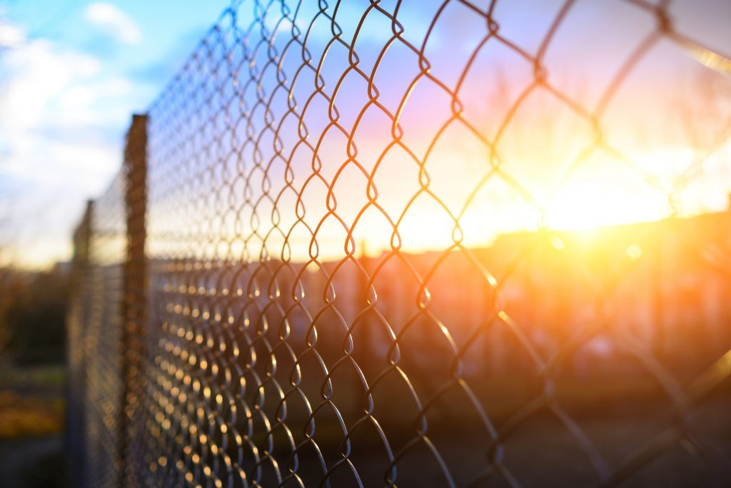 a chain link fence with a pittsburgh sun in the background